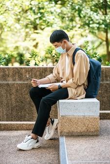 Männer mit masken sitzen und lesen bücher auf der treppe.