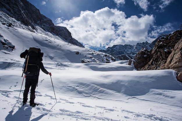 Männer mit rucksack gehen am sonnentag auf den gipfel des berges