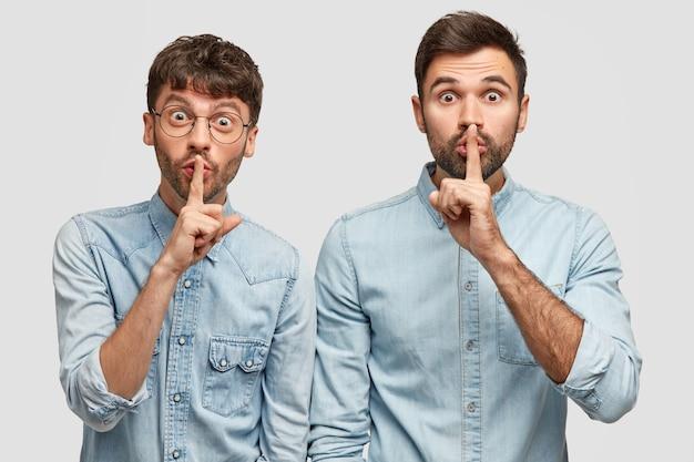 Männer mit schockiertem gesichtsausdruck zeigen ein zeichen der stille, stehen zusammen an einer weißen wand und tragen jeanskleidung