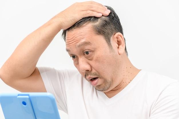 Männer mittleren alters sorgen sich um haarausfall oder haarwuchs isoliert einen weißen hintergrund,