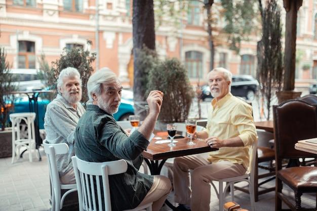 Männer rufen kellner an. bärtige grauhaarige männer rufen den kellner an, während sie nach dem trinken in der kneipe um quittung bitten asking