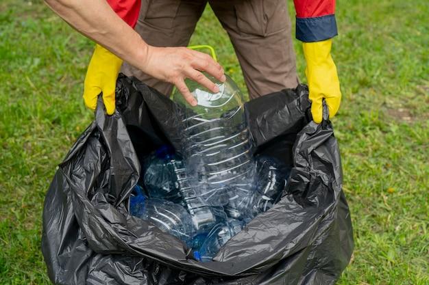 Männer sammeln müll. hand, die eine plastikflasche in einen plastikabfallbeutel einsetzt.
