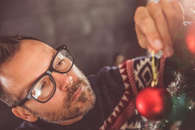 Männer schmücken weihnachtsbaum