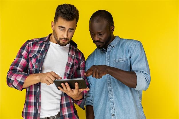 Männer sind überrascht, die tablette zu waschen