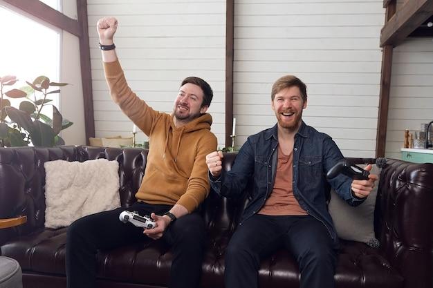 Männer spielen spielekonsole und freuen sich emotional über den sieg, lustige zeit zu hause. hochwertiges foto