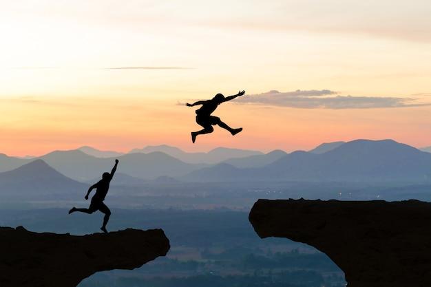 Männer springen klippen sonnenlicht über silhouette