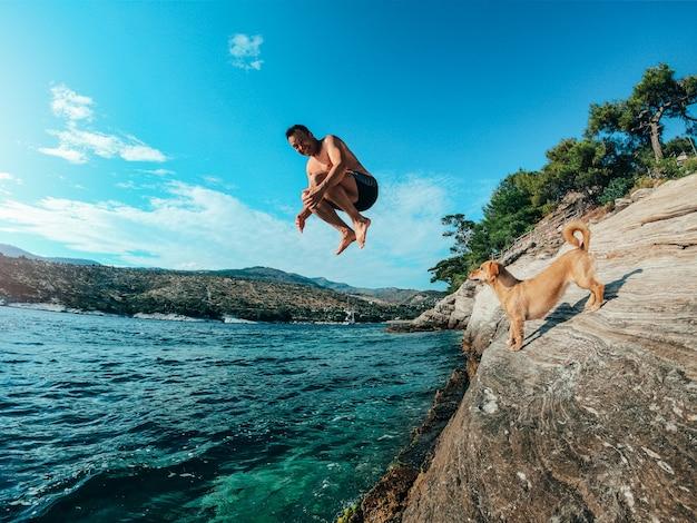 Männer springen vom felsigen ufer ins meer