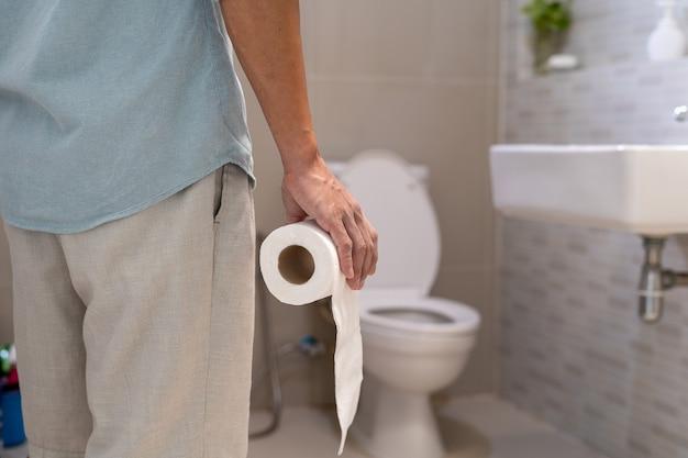 Männer stehen mit starken bauchschmerzen oder durchfall vor der badezimmertür und halten sich mit den händen den bauch fest. das konzept von magenkrämpfen, durchfall