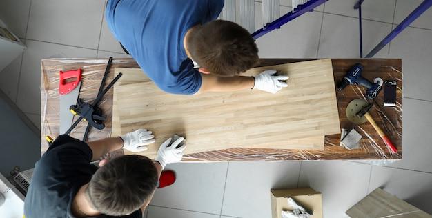 Männer tischler polieren holzoberfläche leinwand auf tisch. installation auf der oberflächenwerkbank verschiedene werkzeuge zur bearbeitung von werkstücken. spezielle tischlerwerkzeuge und entsprechend ausgestatteter arbeitsplatz