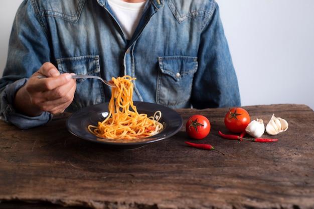 Männer tragen die hemden, die einen spaghetti mit einem löffel halten, der auf einen holztisch gesetzt wird