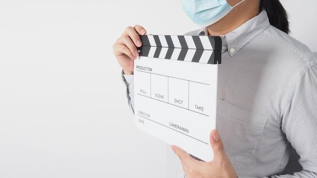 Männer tragen gesichtsmaske und hemd und halten klappbrett oder filmschiefer. es verwendet in der videoproduktion und in der kinoindustrie auf weißem hintergrund.