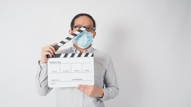 Männer tragen hemd und gesichtsmaske und halten klappbrett oder filmschiefer. es verwendet in der videoproduktion und in der kinoindustrie auf weißem hintergrund.