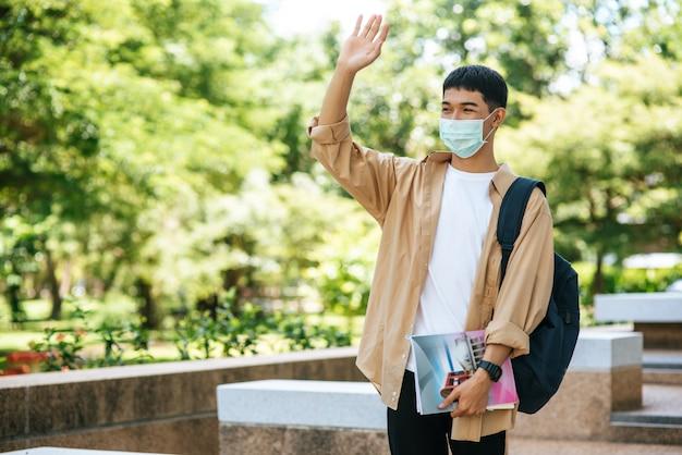 Männer tragen masken, tragen bücher und tragen einen rucksack auf der treppe.