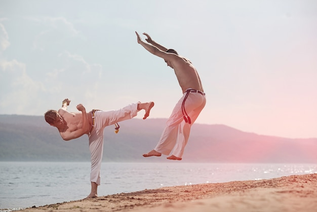 Männer trainieren capoeira am strand
