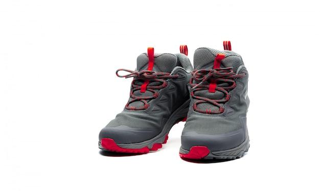 Männer trekkingschuhe isoliert. graurote wanderschuhe. sicherheitsschuhe zum klettern. abenteuerausrüstung. leichte gummi-trekkingschuhe mit sicherheitssohle.