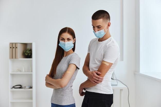 Männer und frauen, die im krankenhaus-kovid-pass nebeneinander medizinische masken tragen