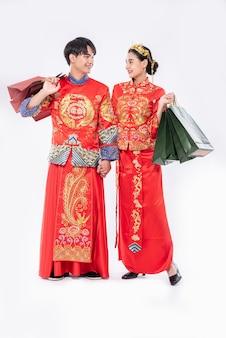 Männer und frauen, die qipao tragen, gehen mit papiertüten einkaufen.