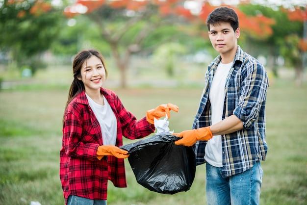 Männer und frauen helfen sich gegenseitig beim sammeln von müll.