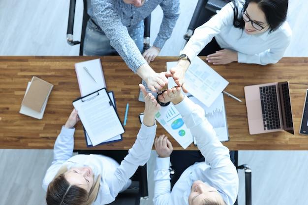 Männer und frauen im büro an ihrem schreibtisch geben sich gegenseitig fünf hände. entwicklung von geschäftskonzepten