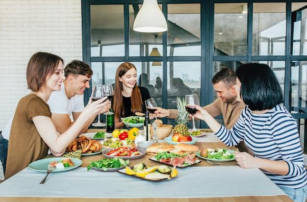 Männer und frauen in der küche sitzen mit gläsern wein in den händen an einem gedeckten tisch und lachen und reden