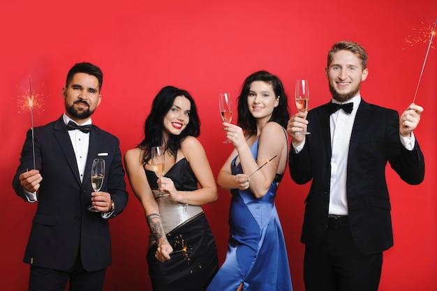 Männer und frauen mit wunderkerzen und champagner