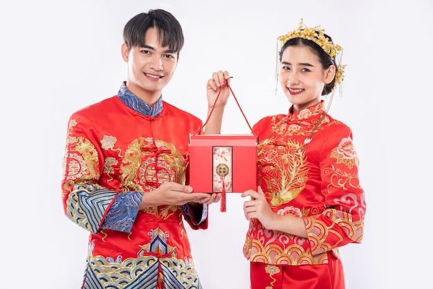 Männer und frauen tragen cheongsam stehend mit roten taschen