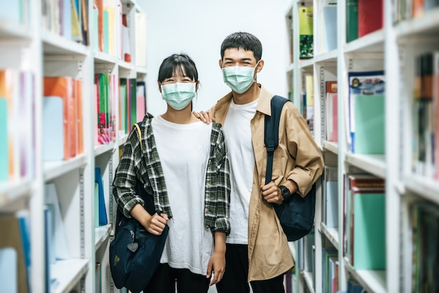 Männer und frauen tragen einen rucksack und suchen in der bibliothek nach büchern.
