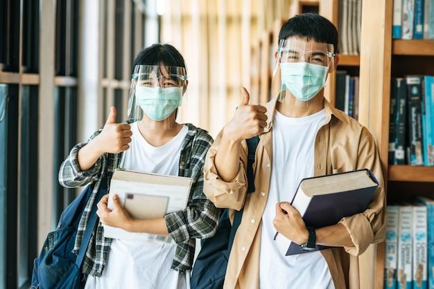 Männer und frauen tragen masken, um zu stehen, bücher in der bibliothek zu halten und die daumen hochzulegen.