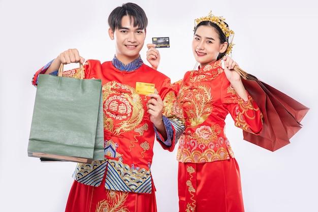 Männer und frauen tragen qipao, tragen papiertüten und gehen mit kreditkarten einkaufen.
