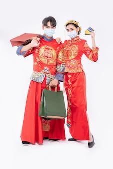 Männer und frauen tragen qipao und gesichtsmasken, papiertüten, gehen mit kreditkarten einkaufen.