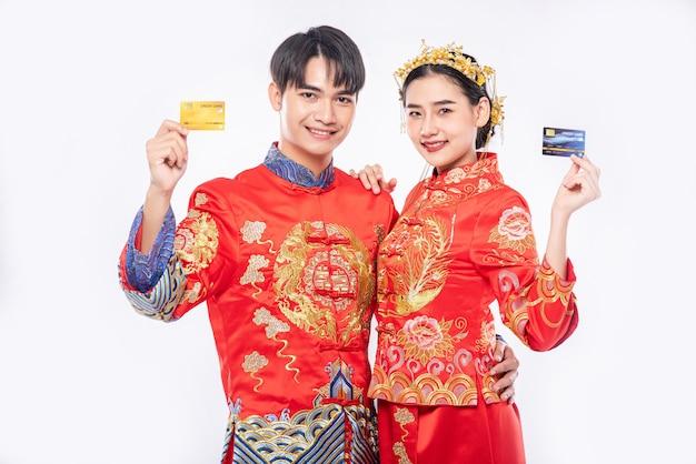 Männer und frauen tragen sie ein qipao und gehen sie mit einer kreditkarte einkaufen.