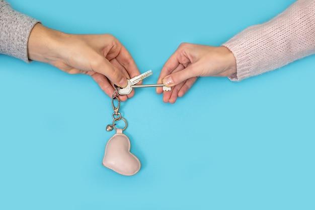Männer- und frauenhände, die neuen schlüssel mit herz vom haus auf blau halten.