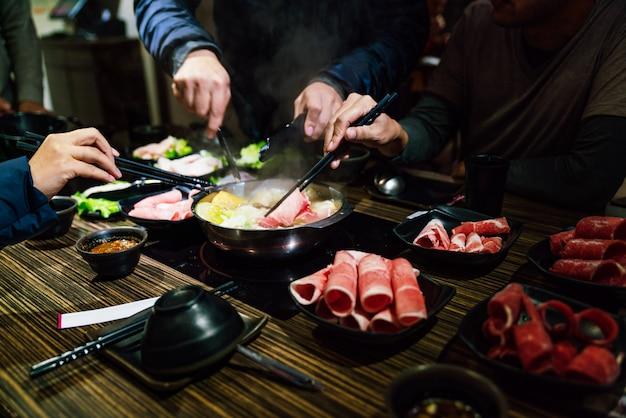 Männer- und frauenhände, die wagyu a5-rindfleisch und kurobuta-schweinefleisch in einer mittelgroßen, seltenen scheibe im heißen topf shabu kneifen.