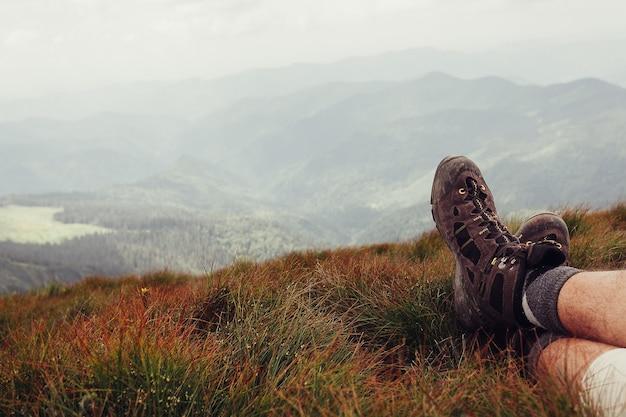 Männerbeine in den braunen schuhen, die auf dem berg liegen
