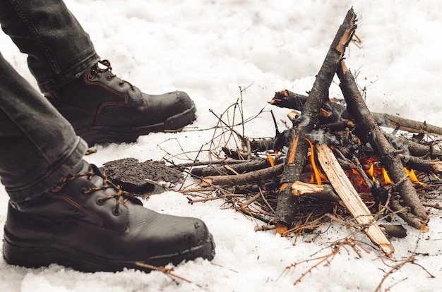 Männerbeine in schwarzen wanderschuhen nahe einem brennenden lagerfeuer.