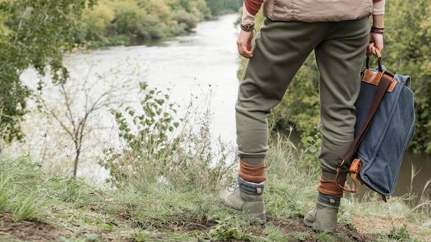 Männerfüße, die auf gras stehen und rucksack halten