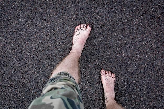 Männerfüße sind auf dem vulkanischen schwarzen sand.