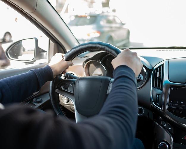 Männerhände am lenkrad des autos