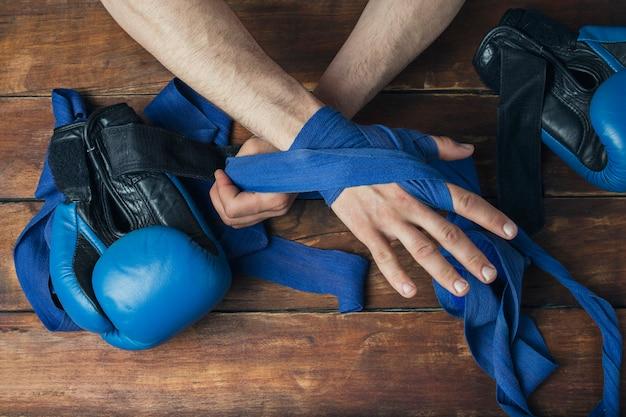 Männerhände beim aufkleben vor einem boxkampf gegen eine holzoberfläche. das konzept des trainings für boxtraining oder kampf. flache lage, draufsicht
