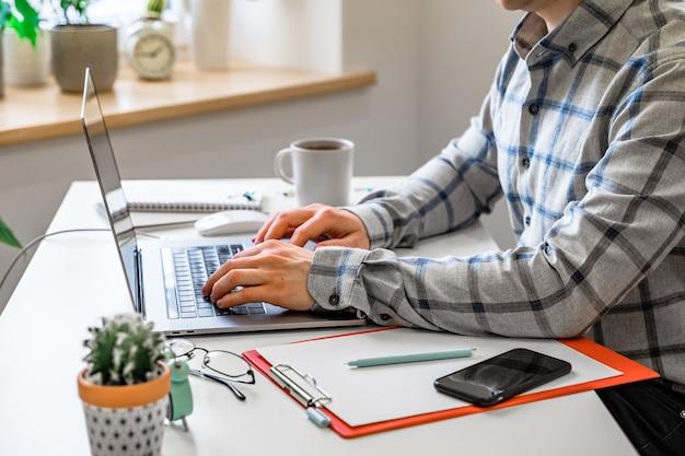 Männerhände, die auf einer laptoptastatur ein geschäftskonzept der arbeit im büro tippen