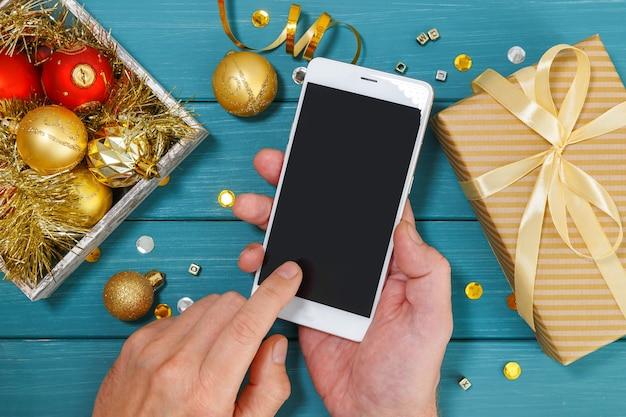 Männerhände, die ein smartphone über weihnachtsdekorationen und geschenkbox halten