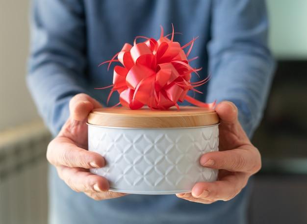 Männerhände, die eine geschenkbox mit verzierung anbieten. nahaufnahme. valentinstag, jubiläum, geburtstagskonzept. speicherplatz kopieren.