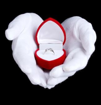Männerhände, die ring im kasten auf schwarz halten