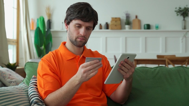 Männerhände halten ein tablet, ein mann sitzt in einem raum mit einem tablet und verbringt seine freizeit damit, online zu chatten und websites zu durchsuchen