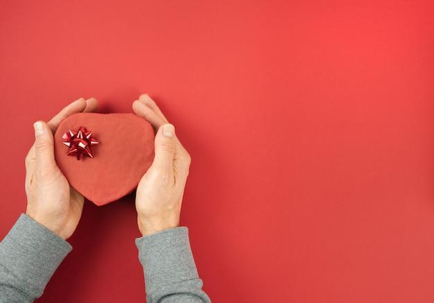 Männerhände halten herzförmige geschenkbox, die mit verzierung auf rotem hintergrund geschlossen wird. valentinstag