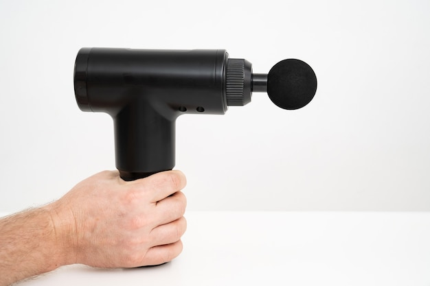 Männerhände halten massagepistole. medizin-sportgerät hilft muskelschmerzen nach dem training zu reduzieren