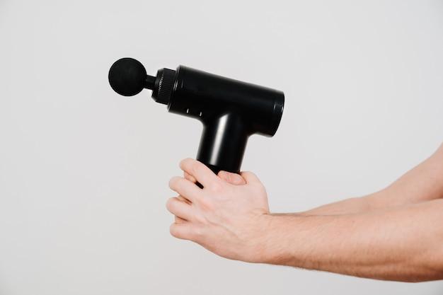 Männerhände halten massagepistole.