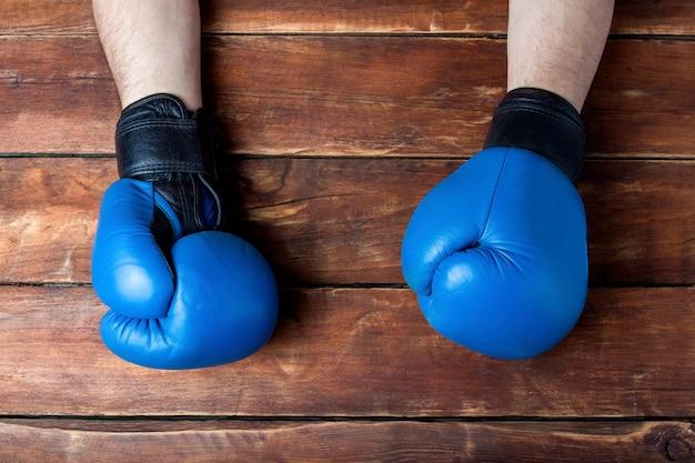 Männerhände in den boxhandschuhen auf einem hölzernen hintergrund. bereit geste. konzept des trainings für boxtraining oder kampf.