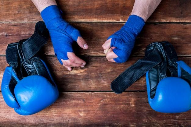 Männerhände in den boxverbänden und in den boxhandschuhen auf einem hölzernen hintergrund. konzeptvorbereitung für boxtraining oder kampf.
