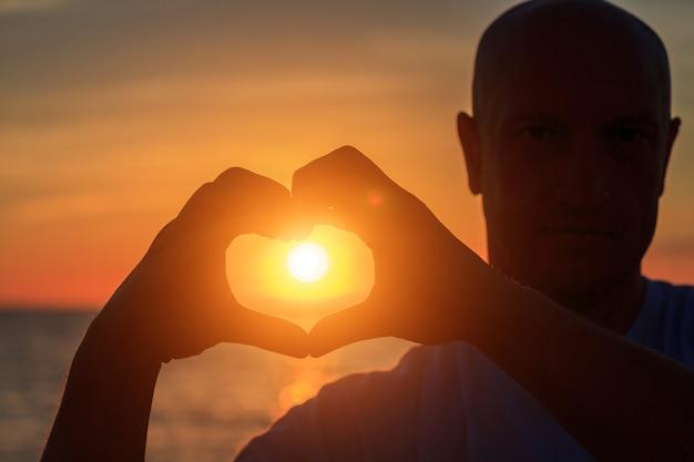 Männerhände in form von herzen gegen sonnenlicht im sonnenunterganghimmel